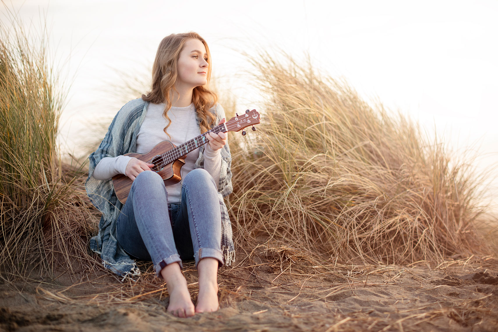 Teen girl playing ukulele in dunes